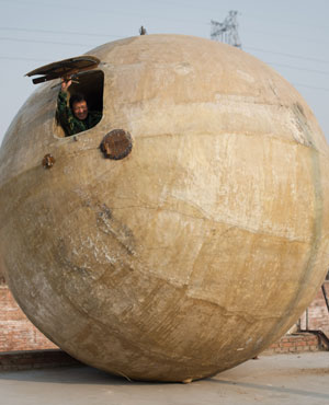 "Farmer Liu Qiyuan looking out from a survival pod that he built and also dubbed ""Noah's Arc"". (Ed Jones, AFP)"