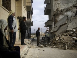 Syrian men break the concrete of a residential building destroyed in a government airstrike. (Muhammed Muheisen/AP)